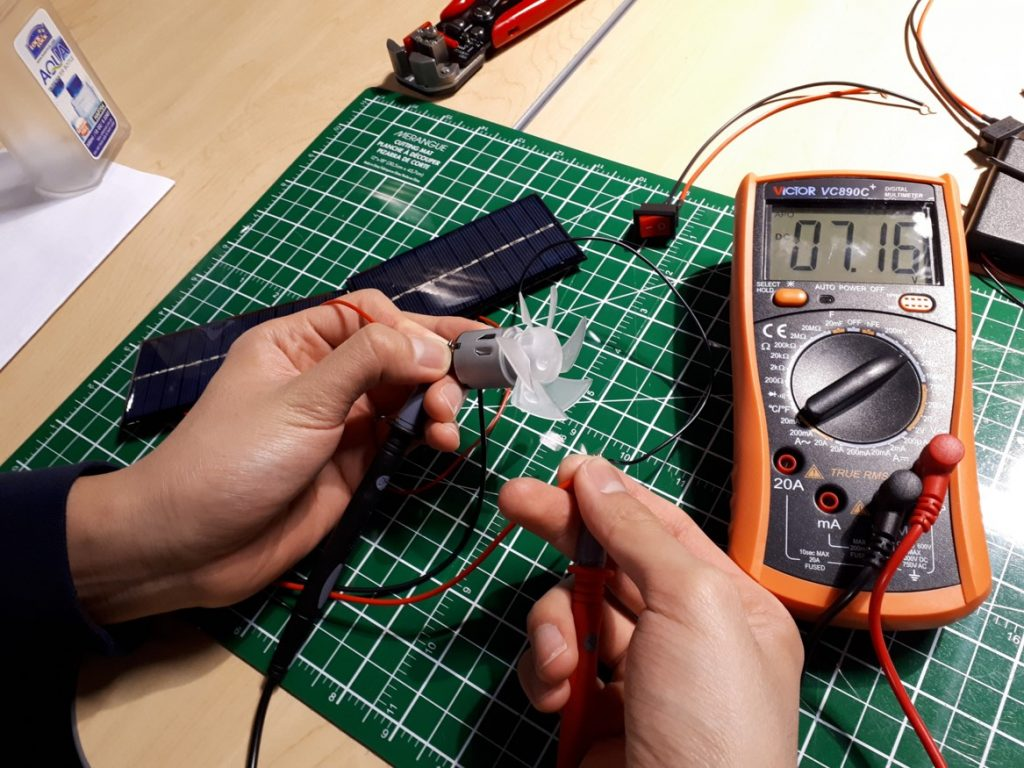 Text Box: Figure 7. When the voltage was measured at the (+) motor ring (left hand) and at the coiled connection between the on/off switch wire and the (-) hookup wire (right hand) a voltage reading was produced on the multimeter.